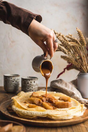 Crêpes au caramel beurre salé et pommes. Caramel en train d'être versé.