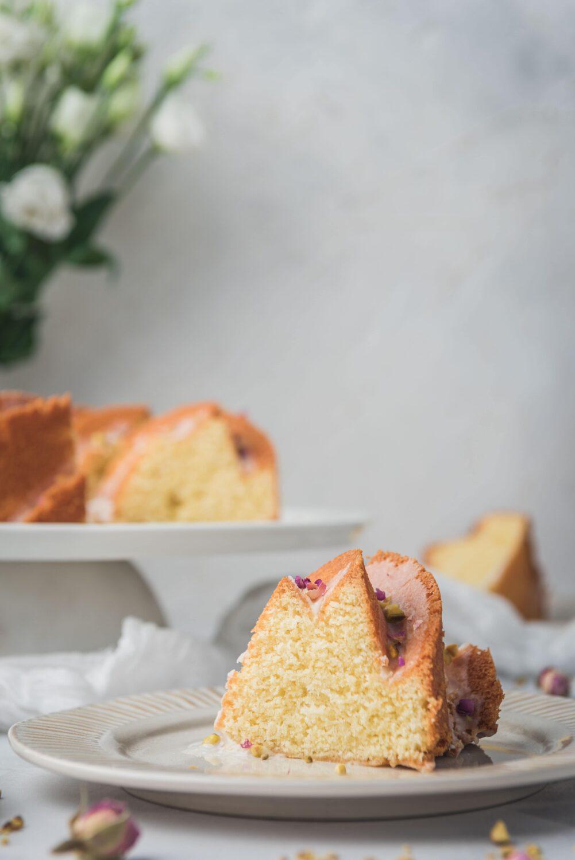La découpe du bundt cake avec un glaçage à la rose et à la pistache - food photography